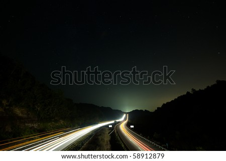 Traffic moving along interstate under starry sky toward glowing city beyond ridge. - stock photo
