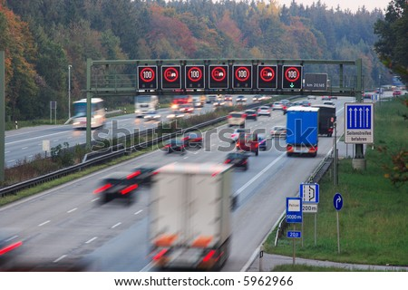 traffic on german autobahn with speed limit sign, motion blur - stock photo