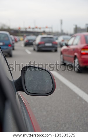 Traffic on highway captured from car window. Visible side view mirror - stock photo