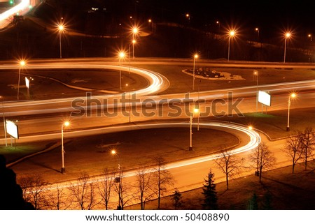 traffic on night road junction with long exposure - stock photo