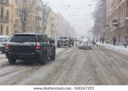 traffic on the snowy street of a modern European city