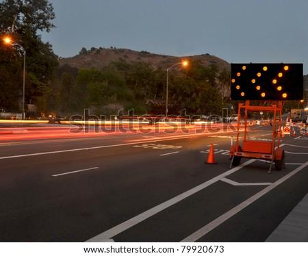 traffic passing by construction/Night Traffic Warning/Night traffic passing by a warning sign - stock photo