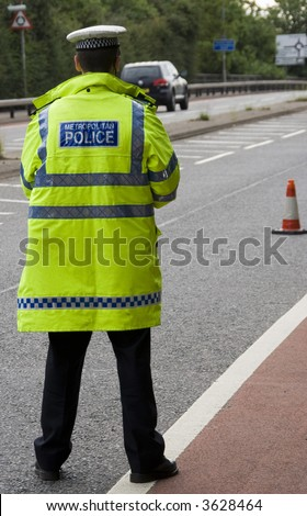 Traffic police officer waits standing in the road looking for on coming vehicles - stock photo