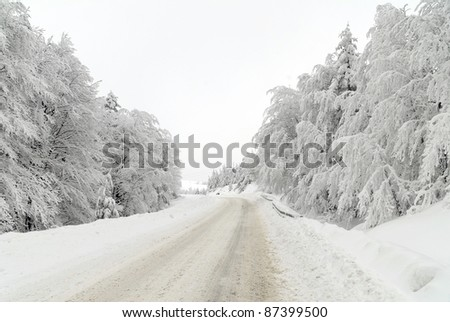 Traffic road in frost and snow, mountain, forest - stock photo
