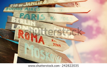 traffic road  sign including Moscow, Roma,London,Berlin,Paris,Buenos Aires, Rio de Janeiro on blue sky background - stock photo