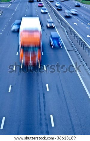 Traffic road with orange truck, motion blur - stock photo