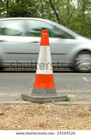 traffic safety cone and speeding automobile - stock photo