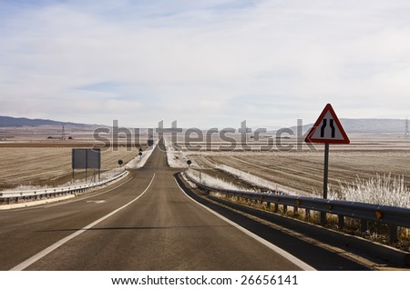 Traffic sign before rural road through frozen plains. - stock photo
