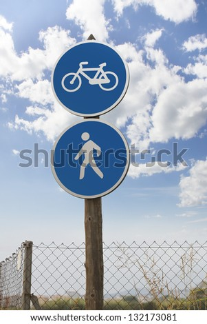 Traffic sign, bicycle path and pedestrian on blue sky background