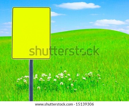 Traffic sign: clover meadow and a hill on the cloudscape horizon