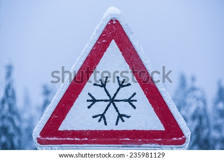 Traffic sign for icy road covered with ice - stock photo