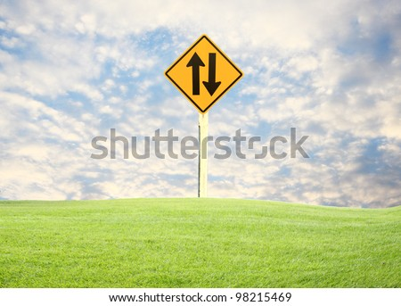 traffic sign, green grass clouds blue sky