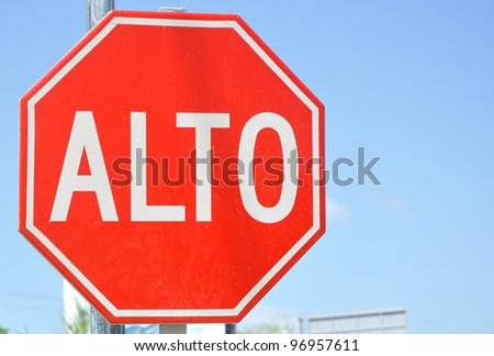 Traffic Sign in Spanish (Alto) and English (English) - stock photo