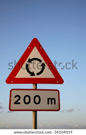 Traffic sign indicating a roundabout 200m ahead against a blue sky with copy space.