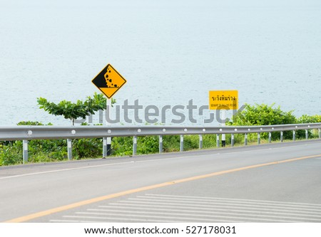 traffic sign placed beside along the road , Steep Hill Descent, Steep Hill Ascent, Speed Limited (30km/ h), Maze, Left Winding Road, Steep Hill Descent , Falling rock,beside sea