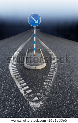 Traffic sign with arrow on road leading into blue haze