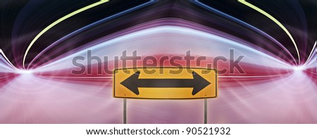 Traffic sign with double arrows pointing in both left and right direction. in urban highway road tunnel with blurred lights motion. Computer generated colorful illustration. - stock photo