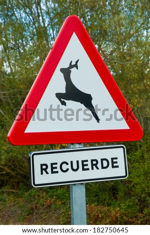 Traffic signal with added poster with text, remember, in Spanish. Danger deer.