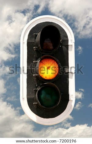 Traffic signals with amber light on against a cloudy sky - stock photo
