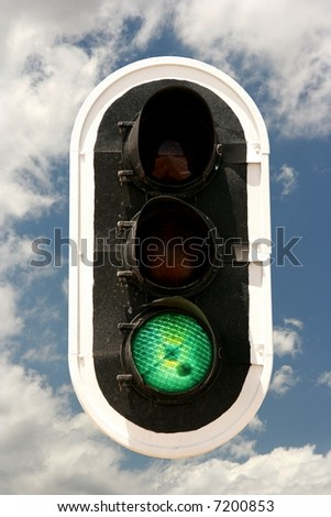 Traffic signals with green light on against a sky with clouds - stock photo