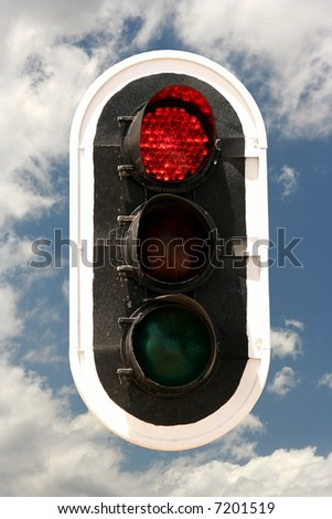Traffic signals with lights on red against a blue sky with clouds - stock photo