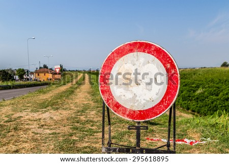 traffic signs and country roads - a faded speed limit 30 mph sign become a sign prohibiting access to the trail on the bank of a river - stock photo