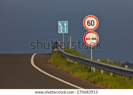 Traffic signs on the side of a road with stormy sky background - stock photo