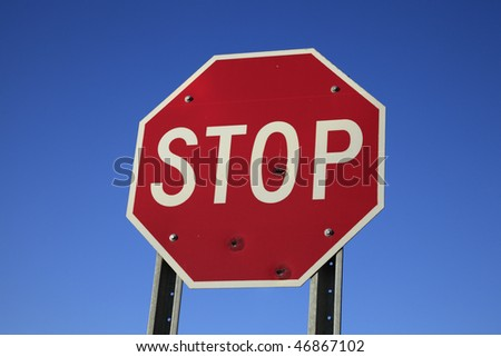 Traffic stop sign against blue sky.