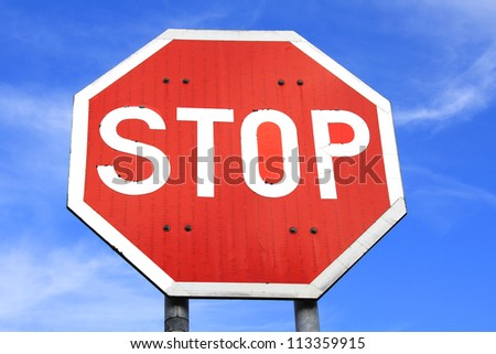 Traffic stop sign against blue sky with some clouds. - stock photo