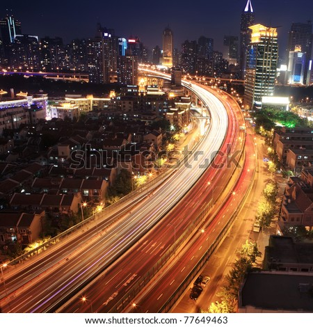 traffic through downtown at night - stock photo
