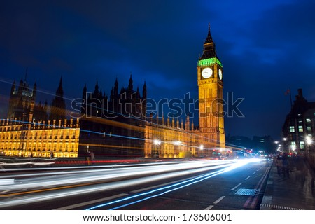 Traffic through London. Big Ben, one of the most prominent symbols of both London and England, as shown at night along with the lights of the cars and busses passing by - stock photo