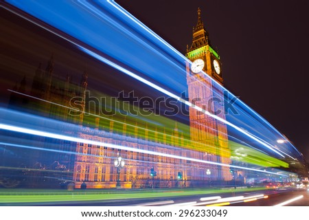 Traffic through London. Big Ben, one of the most prominent symbols of both London and England, as shown at night along with the lights of the cars and buses passing by. - stock photo