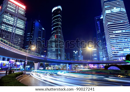 traffic through modern city at night in shanghai - stock photo