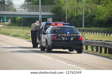Traffic Ticket Police Vehicle - A police cruiser with the lights flashing has stopped a speeding car along the interstate highway and is issuing a ticket. - stock photo
