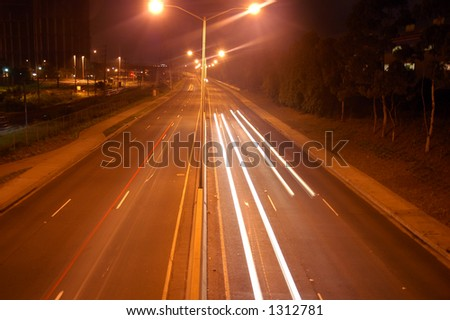 Traffic trail of car headlights at night - stock photo