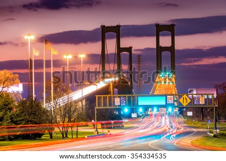 Traffic trails on Delaware Memorial Bridge at dusk. DMB is a set of twin suspension bridges crossing the Delaware River between NJ and DE states, dedicated to WWII, Vietnam and Korean war heroes. - stock photo