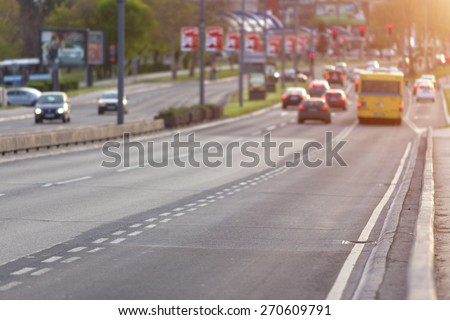Traffic with cars and bus on city boulevard towards the crossroad with red light opposite the setting sun. Shallow depth of field, focus on asphalt in the foreground. - stock photo