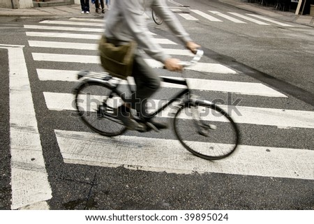 Traffic with speedy cyclist passing crosswalk. - stock photo