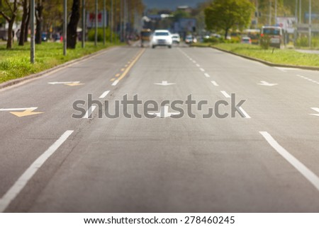 Traffic with white car on city boulevard towards the crossroad with many arrow signs in foreground. Shallow depth of field, focus on arrow signs in the foreground. Belgrade - Serbia - stock photo