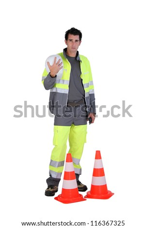 Traffic worker stood by cone - stock photo