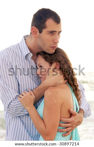 tragic young couple outside, man is holding woman close, comforting her, he looks concerned, she is holding him - stock photo