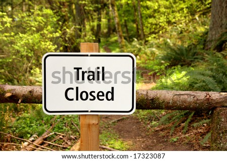 Trail closed sign along path in the woods - stock photo