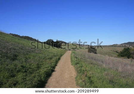 Trail leading through a grassy field, California - stock photo
