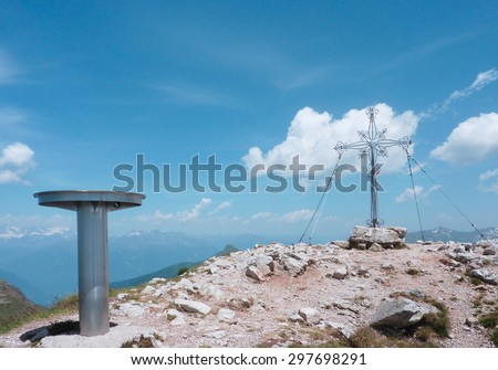Trail marker for hikers and cross on the summit of the mountain. - stock photo