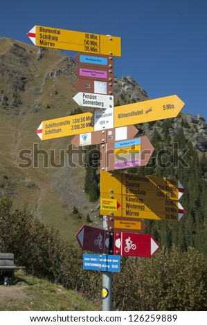 Trail marker on Swiss hike pointing in various directions with mountain in background - stock photo
