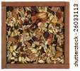 trail mix with pumpkin, sunflowers seeds, almonds, dried papaya,  cranberries, raisins, apples, Brazilian nuts in a rustic wooden box or frame  isolated on white - stock photo