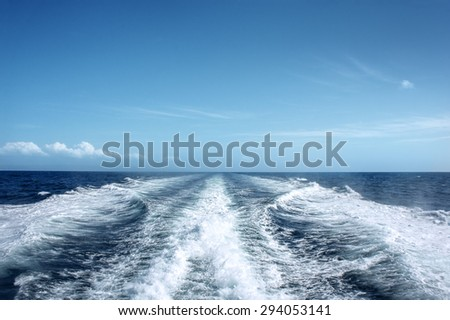 Trail on water surface behind of fast moving motor boat - stock photo