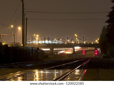 Trail rails in the rain with red lights in the distance and an overpass - stock photo