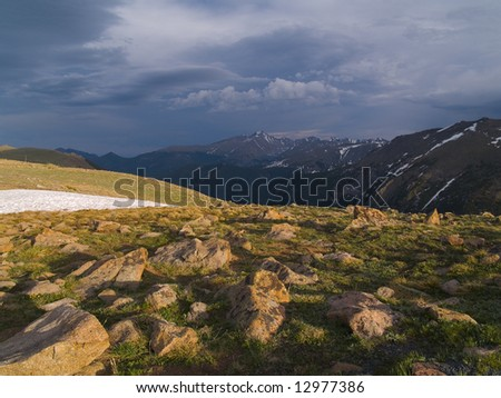 Trail Ridge in Rocky Mountain National Park with evening shadows and a distant storm over Longs Peak. - stock photo