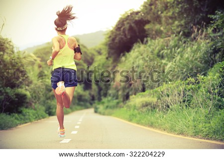 trail runner athlete running on forest trail. woman fitness jogging workout wellness concept.  - stock photo